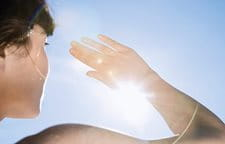 Woman protecting her eyes from sun with her right hand.
