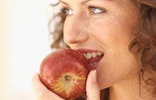 Woman eating an apple.